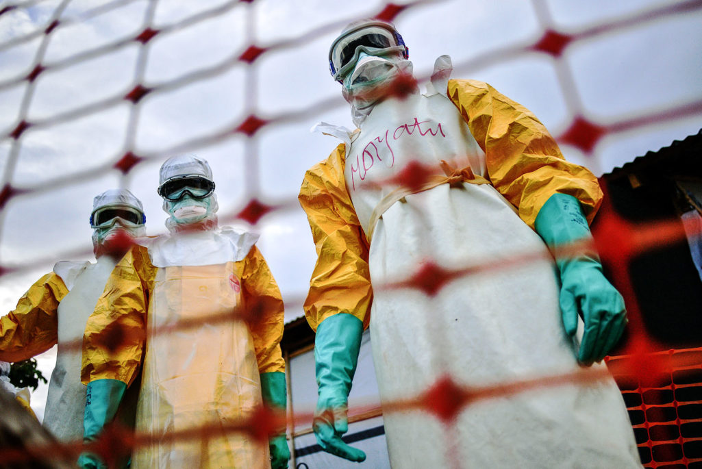 Workers stand over an Ebola victim