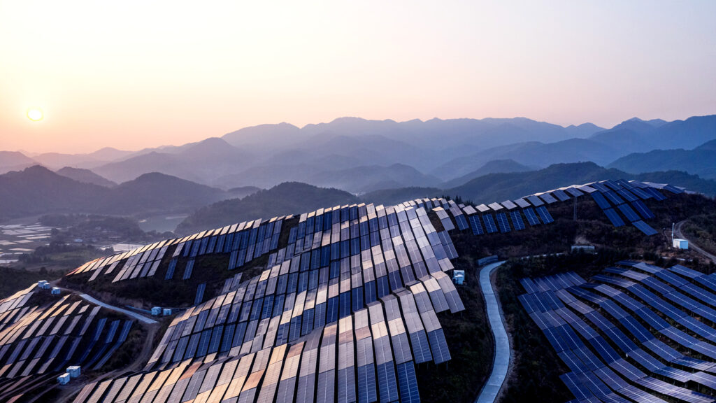Aerial view of the solar power plant on the top of the mountain at sunset