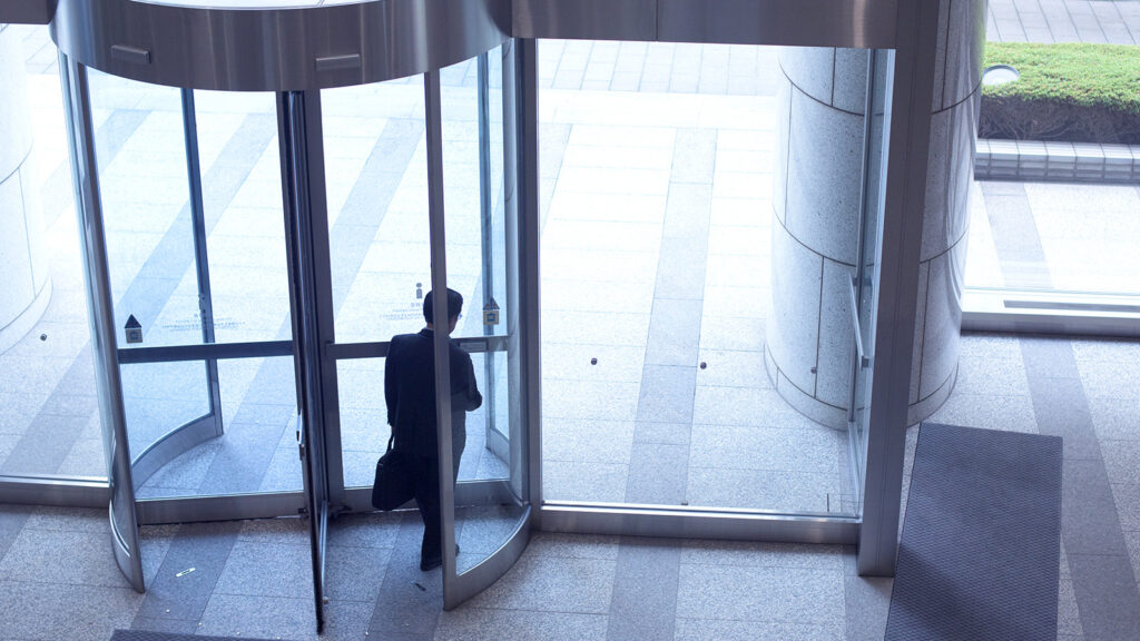 Businessman leaving the revolving door of the office building.